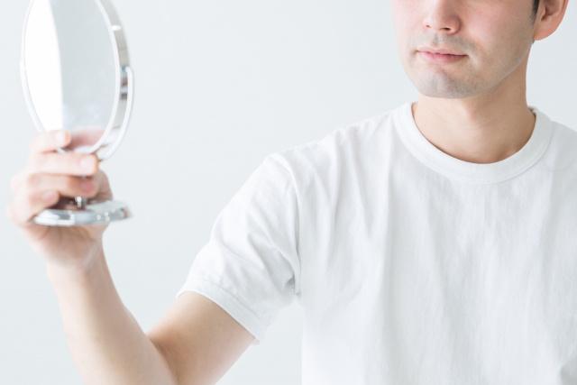 鏡を見る男性